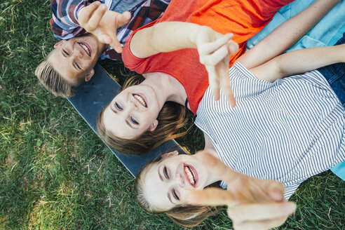 Three happy teenage friends lying on skateboard in meadow making victory sign - AIF000069