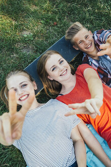 Three happy teenage friends lying on skateboard in meadow making victory sign - AIF000071