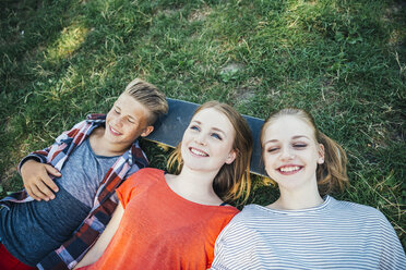 Three happy teenage friends lying on skateboard in meadow - AIF000077