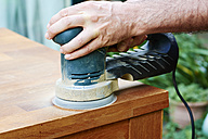 Man sanding an oak table with a random orbital sander, close-up - HAWF000824