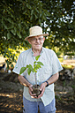 Portrait of smiling farmer with straw hat holding a plant in his hands - RAEF000283