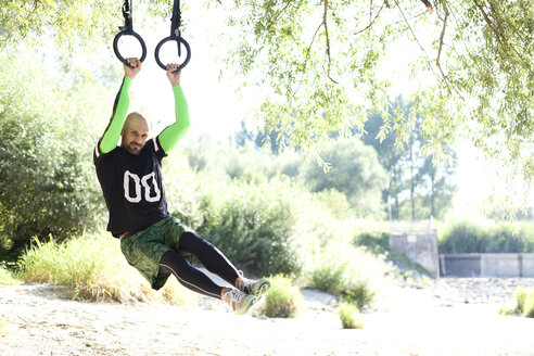 Man doing CrossFit exercise on rings hanging on tree trunk - MAEF010841
