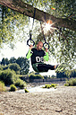 Man doing CrossFit exercise on rings hanging on tree trunk - MAEF010852