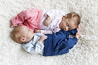 Newborn twins sleeping on white blanket - SHKF000332