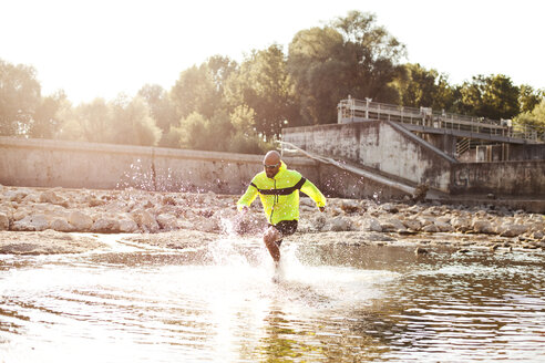 Man in sports wear running in water - MAEF010863