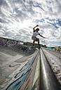 Young man skateboarding in a skatepark - MGOF000423