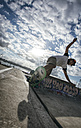 Young man skateboarding in a skatepark - MGO000424