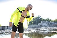 Man in sports wear cheering beside waters - MAEF010881