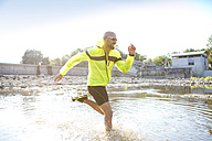 Man in sports wear running in water - MAEF010883