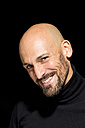 Portrait of smiling bald man with wearing black turtleneck in front of black background - MAEF010890