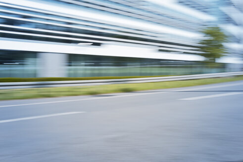 Germany, blurred office building with empty street in the foreground - GUFF000135
