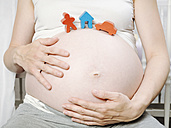 Pregnant woman in front of cot with toy house, toy figurine and toy car on her belly - KRPF001614