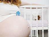 Pregnant woman in front of cot with toy house on her belly - KRPF001612