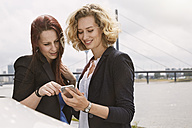 Two young women looking on cell phone at the riverside - STKF001433
