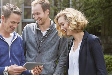 Three happy friends outdoors sharing digital tablet - STKF001383