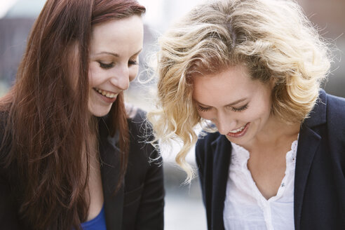 Two young women laughing outdoors - STKF001388