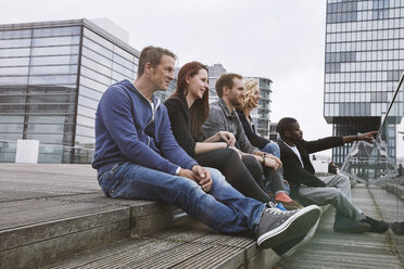 Group of friends sitting outdoors on stairs - STKF001398
