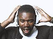 Portrait of screaming young man with headphones - STKF001422