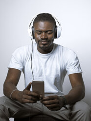 Smiling young man with headphones looking at cell phone - STKF001438