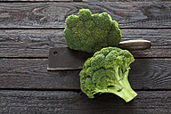 Two broccoli florets and kitchen cleaver on dark wood - CSF026150