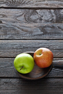 Two apples and wooden spoon on dark wood - CSF026148