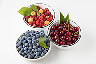 Three bowls of sour cherries, raspberries and blueberries on white ground - CSF026134