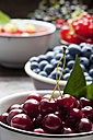 Bowl of sour cherries and bowls of different berries in the background - CSF026128