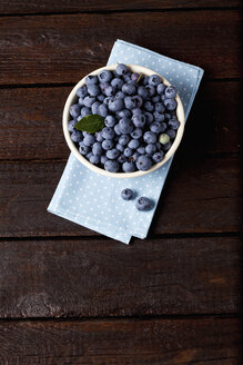 Bowl of blueberries on cloth and dark wood - CSF026119