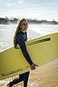 Spain, Colunga, portrait of young woman with surfboard on the beach - MGOF000435
