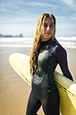 Spain, Colunga, portrait of young woman with surfboard on the beach - MGOF000442