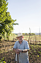 Portrait of farmer with straw hat standing in front of his fields - RAEF000299