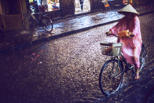 Vietnam, Hoi An, woman on bicycle in rain - EH000149