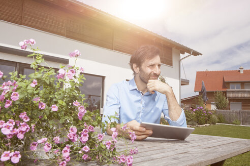 Man with digital tablet in garden - RBF003463