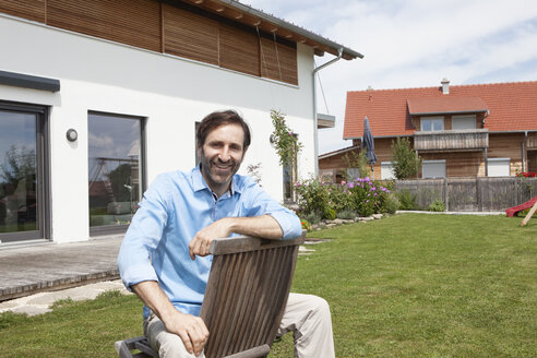 Portrait of smiling man sitting on chair in garden - RBF003467