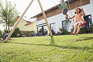Brother and sister on a swing in garden - RBF003432