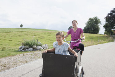 Mother riding bicycle with daughter in trailer - RBF003440