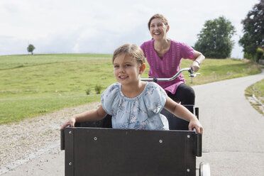 Mother riding bicycle with daughter in trailer - RBF003441