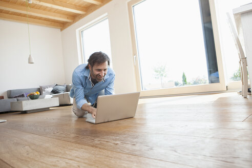 Mature man at home using laptop on the floor - RBF003267