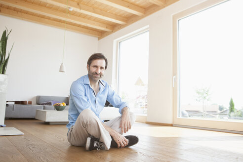 Mature man sitting at home on wooden floor, looking at camera - RBF003344