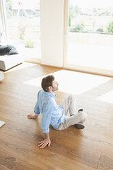Mature man sitting at home on wooden floor, contemplating - RBF003268