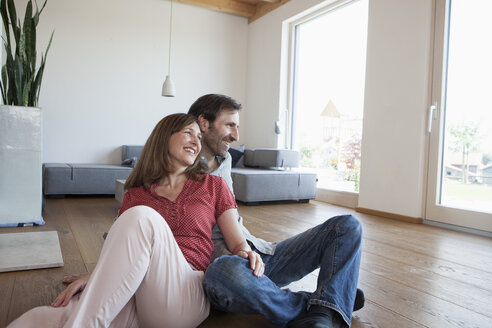 Mature couple sitting on floor, smiling happily - RBF003287
