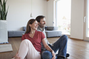 Mature couple sitting on floor, smiling happily - RBF003288