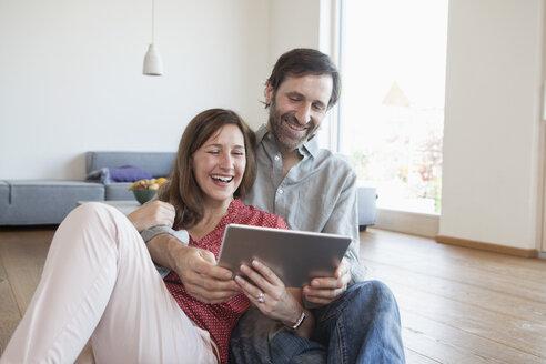 Mature couple sitting on floor, using digital tablet - RBF003290