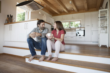 Mature couple sitting on floor, talking about future - RBF003298