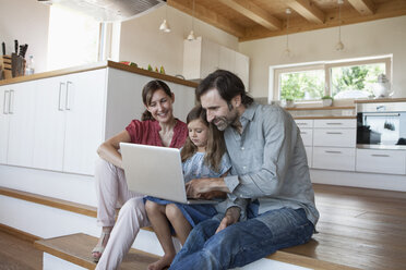 Happy family sitting on kitchen steps, daughter using laptop - RBF003311