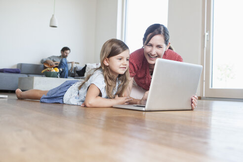 Mother and daughter lying on floor using laptop, father making music in background - RBF003313