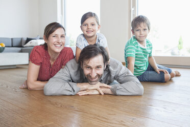 Happy family lying on floor, smiling - RBF003322
