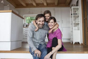 Happy family sitting on kitchen steps - RBF003364