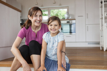 Mother and daughter sitting smiling in kitchen - RBF003335