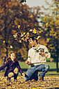 Portrait of happy father and daughter playing with dry leaves in a park - CHAF001259